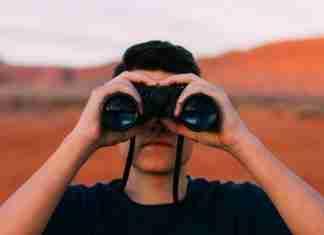 Un giovane guarda l'orizzonte con un binocolo