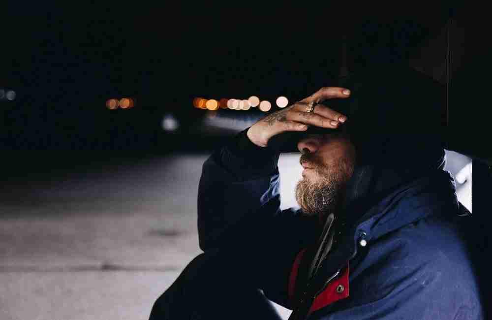 Un uomo disperato seduto a bordo strada